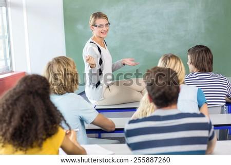 Female teacher teaching students in the class