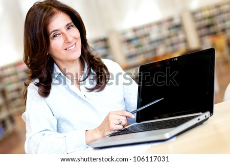 Female teacher with a laptop at the library