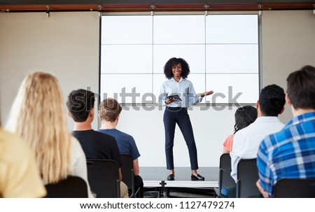 Female Teacher With Digital Tablet Giving Presentation To High School Class In Front Of Screen