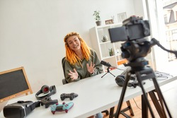 Female technology blogger with dreadlocks smiling and talking while recording video blog or vlog about new gadgets at home. Blogging, work from home concept. Horizontal shot. Dutch angle