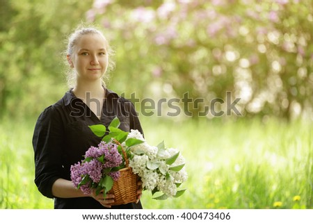 female teen girl hold basket full of lilac flowers, sunny day photo #400473406