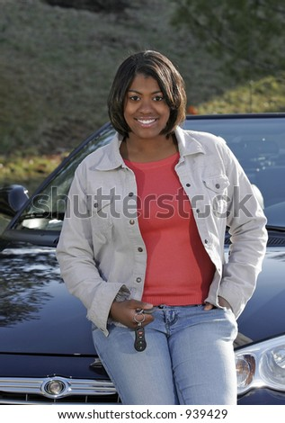 female teen with keys leaning on car