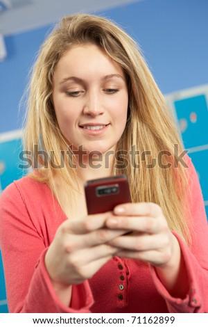 Female Teenage Student Using Mobile Phone By Lockers In School