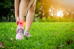 Female teenager hand touching painful twisted or ankle sprain,feel ache,ankle injury after exercise in green nature,asian child girl have leg pain,problem,accident while running,playing in grass park