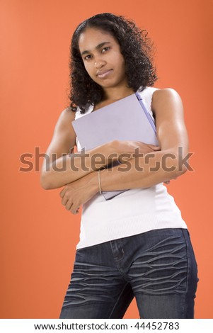 Female teenager posing holding a laptop