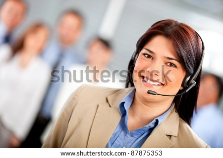 Female telemarketing agent smiling at a call center
