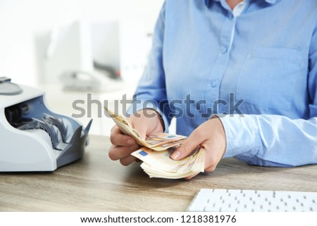 Female teller counting money at cash department, closeup Stock foto ©