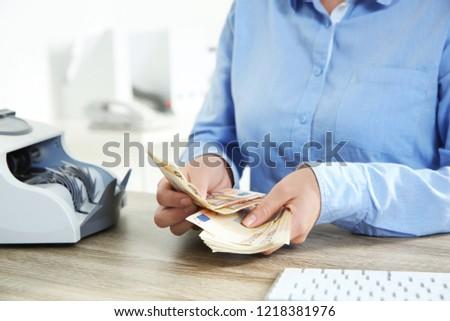 Female teller counting money at cash department, closeup Stock foto ©