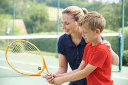 Female Tennis Coach Giving Lesson To Boy