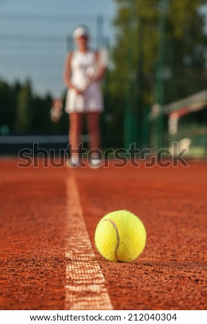 Female Tennis Player And Ball On Tennis Court. Focus Is On Tennis Ball