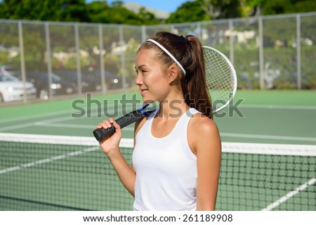 Female tennis player portrait with tennis racket outdoors in tennis court in summer. Fit female athlete playing tennis living healthy active sport and fitness lifestyle. Mixed race Asian Caucasian.