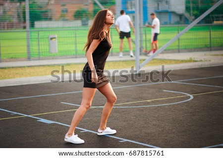 Female tennis player standing with her partner hitting shot in background. Girl play tennis.Sexy tennis girl.Full length portrait of female tennis player serving ball.