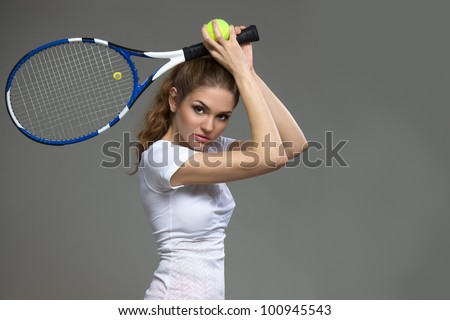 Female tennis player with racket ready to hit a tennis ball.