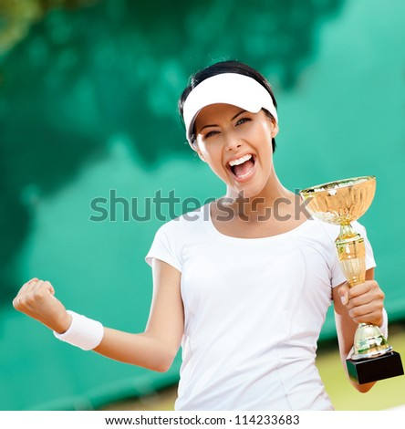 Female tennis player won the cup at the sport competition. Victory
