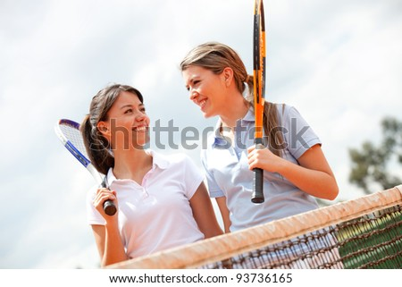 Female tennis players talking at a clay court