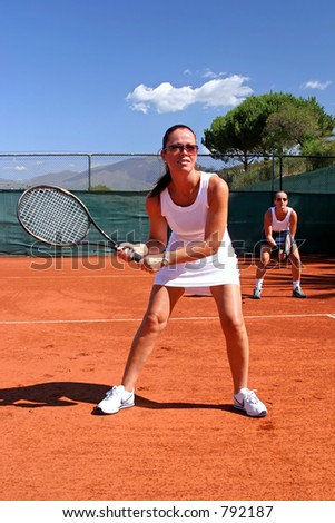 Female tennis players waiting for service on red asphalt court in the sun with blue sky in Spain