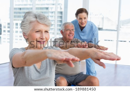 Female therapist assisting senior couple with exercises in the medical office