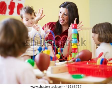 female toddler and 2-3 years girl playing in kindergarten. Horizontal shape - stock photo