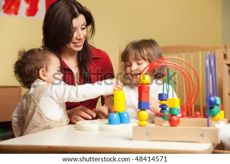 female toddler and 2-3 years girl playing with blocks toy in kindergarten. Horizontal shape