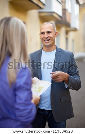 Female tourist asks for directions from man