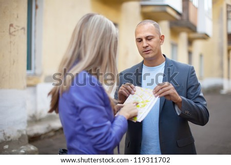 Female tourist asks for directions from man at old city street