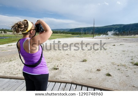 Female tourist at Yellowstone National Park uses a DSLR camera to photograph the scenery