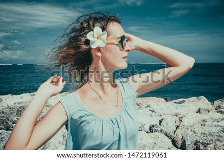 Female tourist enjoying sunny day on beach. Skincare sun protection concept. Girl enjoy freedom exotic alone vacation. People travel. Windr in wavy hair. Closeup portrait of beautiful woman on sea #1472119061