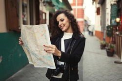 Female tourist exploring city while holding map