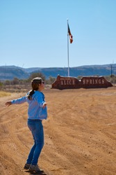 Female tourist full of joy jumping in front of Alice Springs welcome sign and Northern Territory flag. Traveler woman on casual clothes and trekking boots. Alice Springs, Northern Territory, Australia