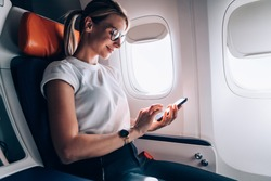 Female tourist in classic eyewear checking received email in social networks during internet messaging on board in jetliner, Caucasian woman booking return tickets connected to high speed wifi