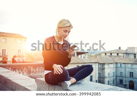 Female tourist is searching information on website via mobile phone about history this beautiful old town. Hipster girl is reading text message on cell telephone, while is sitting on a building roof