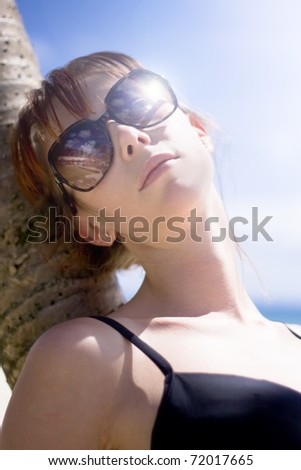 Female Tourist On Holiday Resting Against A Tropical Island Palm Tree On A Summer Beach In A Serene Portrait Of Peaceful Calm When Living A Traveling Lifestyle