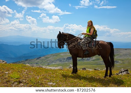 Female tourist on horseback at mountains