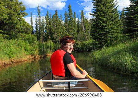 Female tourist paddling a canoe on the mountain lake and blurred green wood in the background. Vermilion Lakes. Banff National Park, Alberta, Canada)