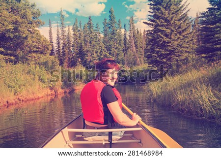 Female tourist paddling a canoe on the mountain  lake. Vermillion Lakes. Banff National Park, Alberta, Canada). Image done in vintage retro instagram style