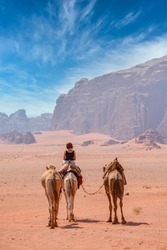 Female tourist riding a camel in the Wadi Rum desert