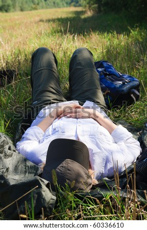 Female tourist taking nap in a field