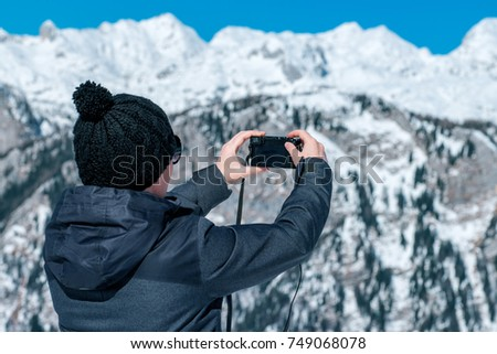 Female tourist taking panoramic picture of beautiful winter mountain landscape with compact digital camera #749068078