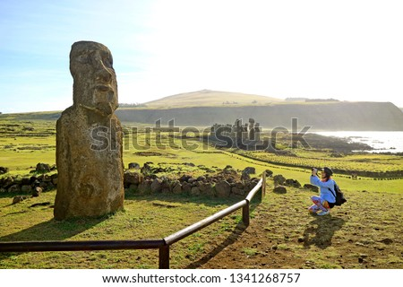 Female tourist taking photo of solitary Moai near the famous 15 Moais on the platform of Ahu Tongariki, Archaeological site on Easter Island, Chile