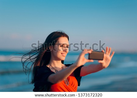Female Tourist Taking Selfies at Sunset by the Sea. Woman taking pictures of herself at the beach in summer holiday