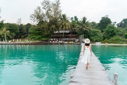 Female tourist walk and chill on wooden bridge as surround sea and beach