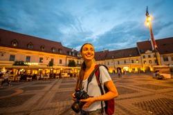 Female tourist walking central square at night in Sibiu, Romania