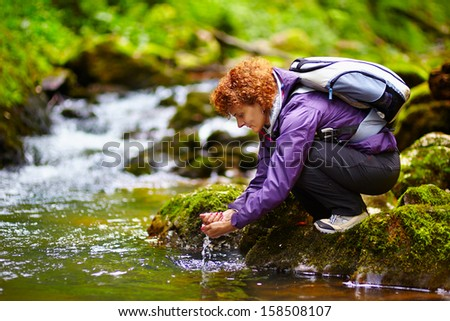 Female tourist washing hands in a mountain river