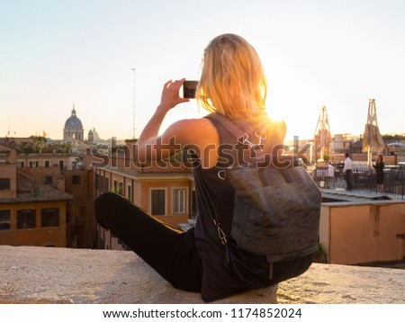 Female tourist with a fashinable vintage hipster backpack taking mobile phone photo of Piazza di Spagna, landmark square with Spanish steps in Rome, Italy at sunset. #1174852024