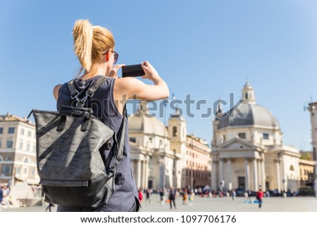Female tourist with a fashinable vintage hipster backpack taking photo of Piazza del Popolo, People's Square, in Rome, Italy by her mobile phone. #1097706176