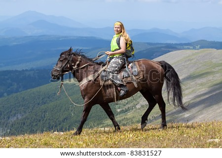 Female tourist with backpack on horseback at mountains