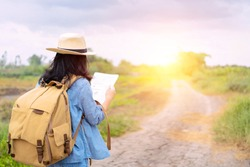 Female tourists are using a map to find the direction of a place. The road is a long way. An adventure trip by yourself with a backpack in the back
