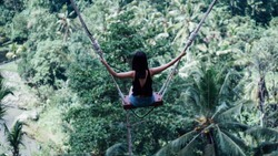 Female tourists playing swing on beautiful natural place in Ubud, Bali, Indonesia.