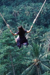 Female tourists swinging on beautiful natural place in Ubud, Bali, Indonesia.