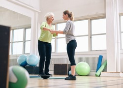 Female trainer helping senior woman in a gym exercising with a bosu balance training platform. Elder woman being assisted by gym instructor while workout session.